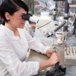 Technician in a dental lab or workshop working under a microscope — Photo
