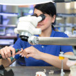 Dental technician producing a prosthesis under a microscope — Stock Photo