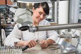 Technician in a dental lab or workshop working under a microscope — Stock Photo