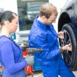 Stockfoto: Two mechanics changing a wheel on a car
