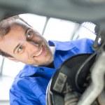 Постер, плакат: Car mechanic repairs the brakes