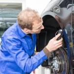 Car mechanic repairs the brakes — Stock Photo