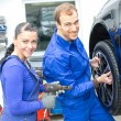 Foto Stock: Two mechanics changing a wheel on a car