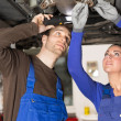 Постер, плакат: Two mechanics repairing a car in hydraulic lift