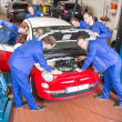 Multiple Auto mechanics repairing a car in garage — Stock Photo