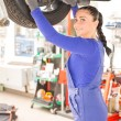 Female mechanic working on car on hydraulic ramp - Stockfoto