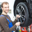 Mechanic changing wheels on a car on hydraulic ramp — Foto Stock