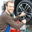 Mechanic changing wheels on a car on hydraulic ramp — Stock Photo #22998042