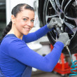 Stockfoto: Mechanic changing wheels on a car on hydraulic ramp
