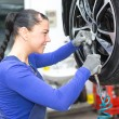Stock Photo: Mechanic changing wheels on a car on hydraulic ramp