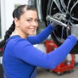 Mechanic changing wheels on a car on hydraulic ramp - Stock Photo