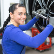 Mechanic changing wheels on a car on hydraulic ramp - Foto Stock