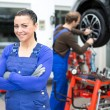 Female mechanic standing in a garage - Stockfoto