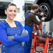 Female mechanic standing in a garage - Stock Photo