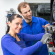 Car mechanics changing wheel working on hydraulic lift - ストック写真
