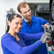 Car mechanics changing wheel working on hydraulic lift - Stock Photo