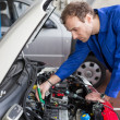 Mechanic repairing a car in a workshop or garage - Stock Photo