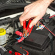 Car mechanic changing the battery - Stock Photo