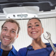 Two mechanics taking a look under the hood of a car — Stock Photo