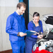 Car mechanics repairing the electrics - Stock Photo