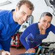 Two mechatronic technicians in a garage - Stock Photo