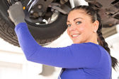 Female mechanic working on car on hydraulic ramp — Stock Photo