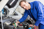 Mechanic repairing a car in a workshop or garage — Photo