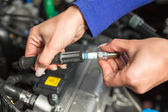 Car mechatronic technician spark plugs — Stock Photo