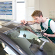 Worker in glazier's workshop installs windshield — Stock Photo #24721641