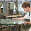 Glazier grinding a pieco of glass - Stock Photo