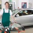 Постер, плакат: Glazier handling car windshield in garage