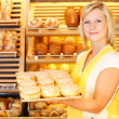 Bakery shopkeeper presents doughnuts - Stock Photo