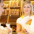 Baker's shop shopkeeper gives bread to customer — Stock Photo