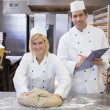Instructor instructing apprentice in bakery — Stock Photo #24722961