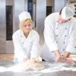 Baker instruction apprentice in kneading bread dough - Stock Photo