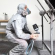 Car body painter spraying paint on bodywork parts - Stock Photo