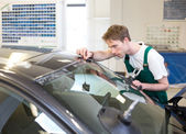 Worker in glazier's workshop installs windshield — Stock Photo