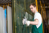 Glazier in workshop handling glass — Stock Photo