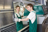 Glazier putting glass in grinding machine — Stock Photo