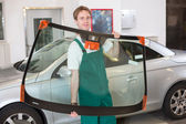 Glazier with car windshield made of glass — Stock Photo