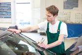 Worker in glazier's workshop installs windshield — Stock Photo