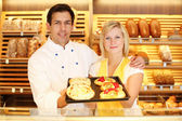 Baker and shopkeeper in bakery with tablet of cake — Stock Photo