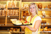 Shopkeeper in baker shop with tablet full of cake — Stock Photo