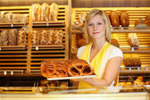 Shopkeeper in bakery with tablet of pretzels — Stock Photo
