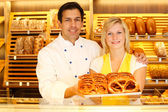 Baker and shopkeeper in a bakery present pretzels — Stock Photo