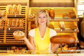 Bakery shopkeeper with two loafs of bread — Stock Photo