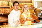 Baker and shopkeeper present pastry — Stock Photo