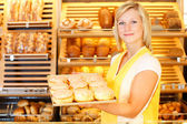 Bakery shopkeeper presents doughnuts — Stock Photo