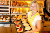 Bakery shopkeeper with cake or pastry — Stock Photo