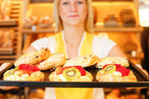 Bakery shopkeeper with tablet of cakes — Stock Photo